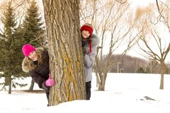 Girl friends behind a tree Royalty Free Stock Images