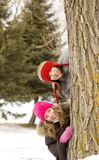 Girl friends behind a tree Royalty Free Stock Photo