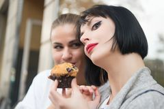 Girl friends with blueberry muffin in paris, france. Women look at cupcake in cafe. Hunger, temptation, appetite concept. Dessert, food, snack, pastry Stock Photo