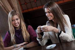 Girl-friends drink coffee in cafe house Royalty Free Stock Photo