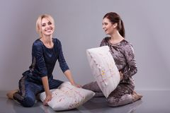 Girl friends fighting on the pillows. Active entertainment. Pijamas party cool active mood festive atmosphere Royalty Free Stock Image