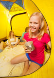 Girl with friends holding cup in camping tent Royalty Free Stock Image