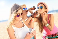 Girl friends on picnic on the beach. A picture of a group of friends drinking beer and texting on the beach Stock Photography