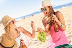 Girl friends on picnic on the beach Stock Photos
