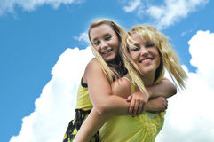 Girl Friends Piggyback Ride. Two beautiful, attractive, happy, carefree blond teenage girls giving each other a piggyback ride in the sunshine with clouds over a Royalty Free Stock Photos