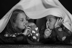 Girl friends play under blanket. Children and pyjamas party concept: kids wearing red jammies Royalty Free Stock Image