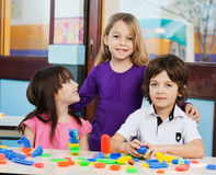 Girl With Friends Playing Blocks In Classroom Stock Photography