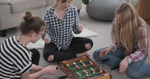 Girl friends playing foosball at home. Cheerful teenage girl friends playing foosball at home stock video footage
