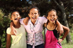 Girl friends share hilarious moment of laughter. Three young school girl friends share a hilarious moment together while in the park in the sunshine Royalty Free Stock Images