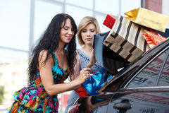 Girl-friends after shopping. Puts their bags in trunk stock photography