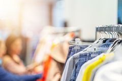 Girl friends shopping for clothes in store stock image
