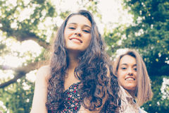 Girl friends sitting on a trunk Royalty Free Stock Images