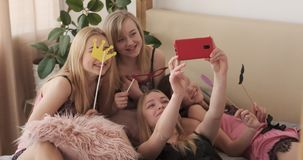 Girl friends taking selfie while posing with fake props on bed. Teenage girls having fun taking selfie while posing with fake props during pajama party at home stock footage