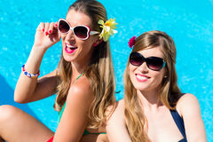 Girl friends tanning at swimming pool in front of water Royalty Free Stock Images