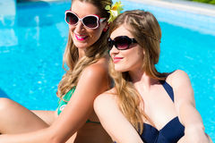 Girl friends tanning at swimming pool in front of water. Girl friends tanning at swimming pool in the sun in front of the water leaning against each other stock images