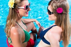 Girl friends tanning at swimming pool in front of water. Girl friends tanning at swimming pool in the sun in front of the water leaning against each other royalty free stock photo