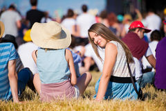 Girl with friends, teenagers, summer festival, sitting on grass Royalty Free Stock Photo