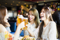 Girl friends toasting and eating in the  restaura Stock Photo
