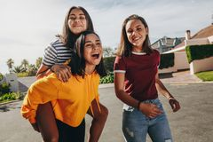 Girl friends walking in the street having fun. Teenage girl piggy riding on her friend walking in the street on a sunny day. Three smiling girls having fun royalty free stock image