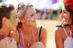 Girl friends wearing face paint at music festival, close up Stock Images