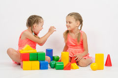 Girl frighten another girl playing with blocks. The four-year and six-year old girl playing in a European-style cubes, isolated on a light background royalty free stock images