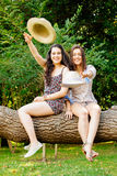 Girl frinds sitting on a trunk throwing hats Royalty Free Stock Images