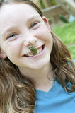 Girl with frog on nose Stock Photos