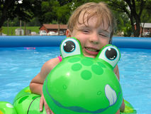 Girl and froggy float. Girl and green froggy float have fun in the pool together Stock Photos