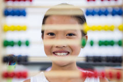 Girl in front of abacus in classroom. Portrait of girl in front of abacus in classroom Royalty Free Stock Photo