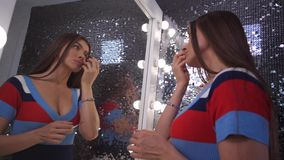 The girl in front of a beautiful mirror makes her makeup. 4K Slow Mo. The girl in front of a beautiful mirror makes her makeup stock video footage