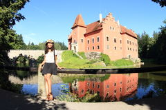 Girl in front of castle Cervena Lhota. Smiling girl - Papuan woman dressed in black skirt and white t-shirt leaning on railing in front of red water castle royalty free stock photos
