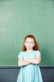 Girl in front of chalkboard in school Stock Image