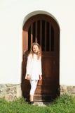 Girl in front of door Stock Image