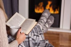 Girl in front of the fireplace reading book and warming feet on fire. Beautiful young woman in front of the fireplace reading book and warming feet on fire and stock images