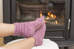 The girl in front of the fireplace in winter socks. And cup of tea stock photo