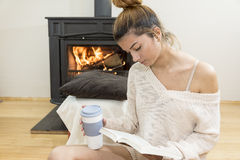 The girl in front of the fireplace in winter socks. And cup of tea royalty free stock photos