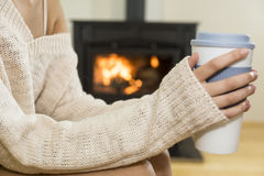 The girl in front of the fireplace in winter socks. And cup of tea Stock Images