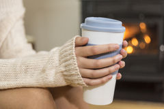 The girl in front of the fireplace in winter socks. And cup of tea royalty free stock image