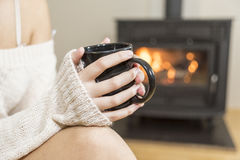 The girl in front of the fireplace in winter socks. And cup of tea royalty free stock images