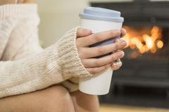 The girl in front of the fireplace in winter socks. And cup of tea Stock Photos