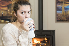 The girl in front of the fireplace in winter socks. And cup of tea Royalty Free Stock Photography