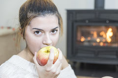 The girl in front of the fireplace in winter socks. And cup of tea Stock Image