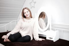 Girl In Front Of A Mirror. A pretty young girl in front of a mirror. Does not every girl need a mirror stock images