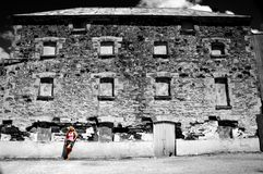 Girl standing in front of old house. A girl in color standing in front of a black and white old house Royalty Free Stock Images