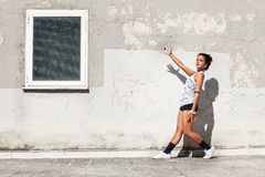 Girl in front of and old wall pointing a window with one arm. A girl in front of an old wall is pointing with one arm a window. She wears shorts and a white T royalty free stock photography