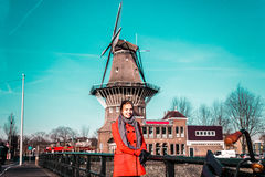 Girl in front of a windmill in Amsterdam, Netherlands royalty free stock images