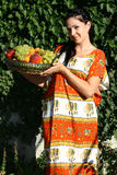 The girl with fruit. The young woman holds a basket with fruit against a twisted ivy Stock Images