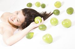 Girl With Fruit 8. A beautiful young asian woman lies on a white floor holding an apple Royalty Free Stock Photography