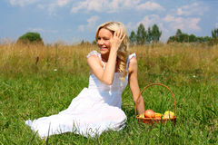 Girl with fruit. Beautiful smiling blonde with a basket of fruit Stock Photography