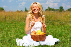 Girl with fruit. Beautiful smiling blonde with a basket of fruit stock image